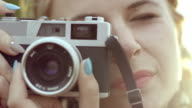 Young woman taking photo with retro camera video
