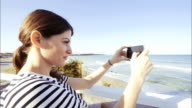 Young woman taking pictures at seashore. video