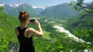 Young woman taking pictures of a mountain valley with smartphone video