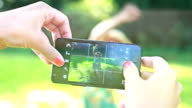 Young woman taking pictures of her friend with phone video