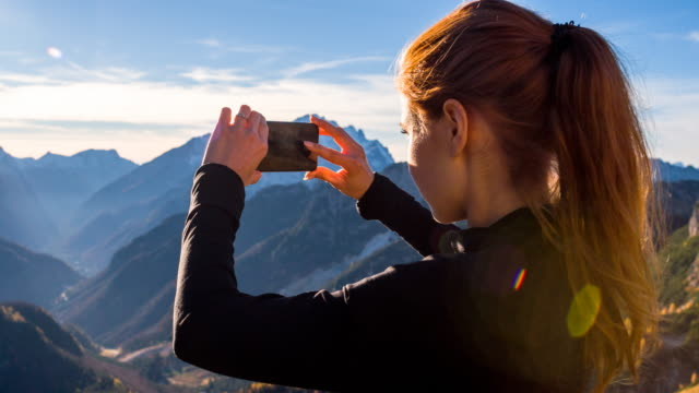 Young woman taking pictures of the beautiful view with smartphone video