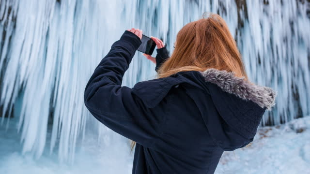 Young woman taking pictures of waterfall in winter video