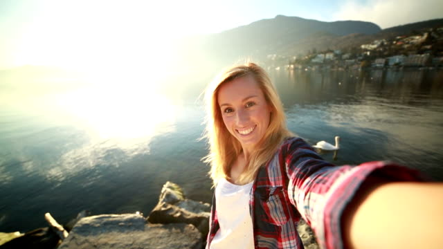 Young woman taking selfie by the lake video