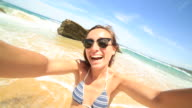 Young woman taking selfie on beach video