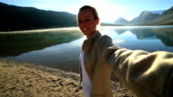 Young woman taking selfie portrait with spectacular mountain lake scenery video