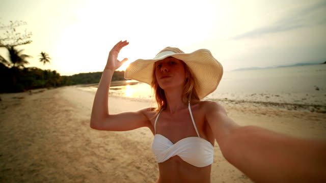 Young woman talking a selfie on tropical beach at sunset video