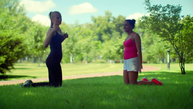Young woman talking kneeling on green grass in park video