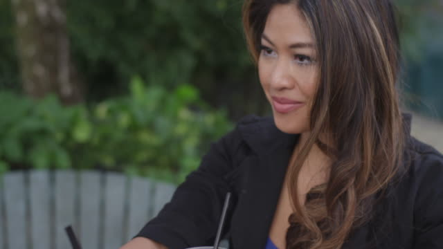 Young woman talking to her date at an outdoor cafe video