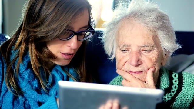 Young woman teaches her grandmother work with computer - senior lifestyle video