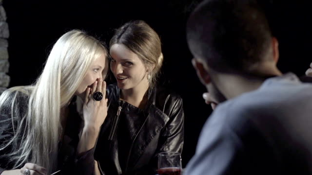 Young woman tell a secret to her friend and smile while enjoying aperitif in outdoor rural scenic at night - slow-motion HD video footage video