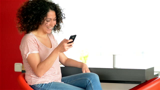 DOLLY: Young woman texting with smart phone at home video