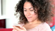 Young woman texting with smart phone at home video