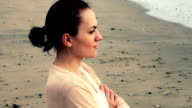 Young woman thoughtfully looking out to sea, steadicam shot video