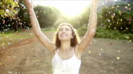 Young Woman throwing confetti in the park in slow motion video