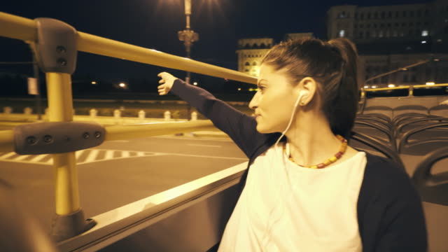 Young woman touring the city on open top bus at night. video