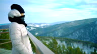 Young woman tourist looks at winter mountains video