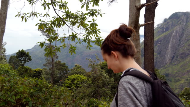 Young woman tourist with backpack walking at trail in mountains with beautiful nature landscape at background. Female hiker going along tropical mount road. Healthy active lifestyle. Travel concept video