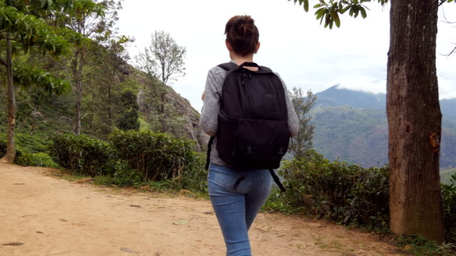 Young woman tourist with backpack walking at trail in mountains with beautiful nature landscape at background. Female hiker going along tropical mount road. Healthy active lifestyle. Summer vacation video