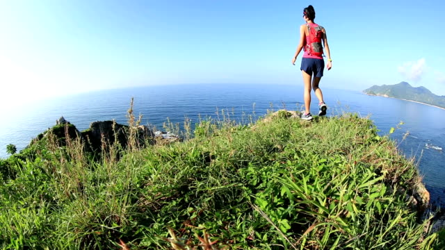 young woman trail runner on seaside mountain peak video