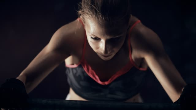 Young woman training on chin-up bar in gym video