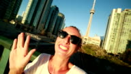 Young woman traveling in Toronto taking selfie portrait with cityscape video