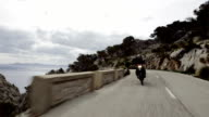 Young woman travelling on a motorcycle. Rocky coastline video