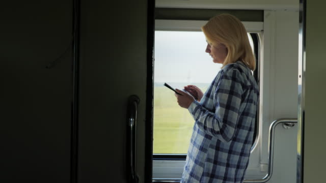 A young woman travels by train, stands by the window, uses a tablet video