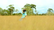 young woman turn around on yellow field video