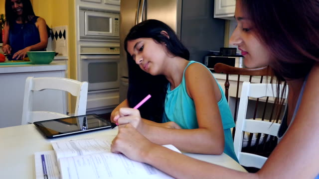 Young woman tutoring her preteen sister at home in family kitchen video
