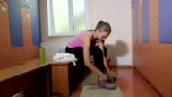 Young woman tying up sneakers in fitness club locker room video