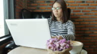 young woman typing keyboard of laptop working at home video