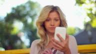 Young woman typing sms and taking photo of herself video