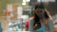 Young woman typing sms on mobile in cafe video
