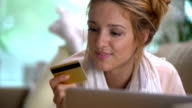 A young woman uses a golden credit card online lying on the couch. Slow motion. video