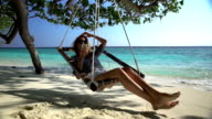 A young woman uses a smartphone and enjoys relaxing on the beach in a hammock. Slow motion. video
