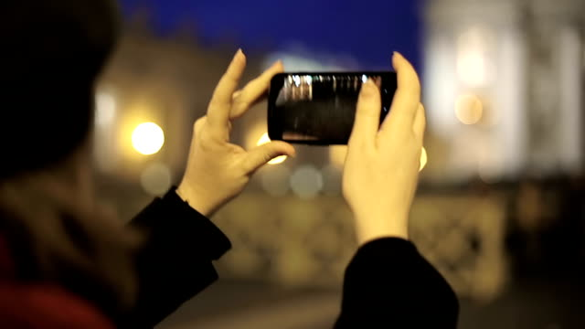 Young woman uses a smartphone to capture a Saint Peter Basilica image video