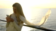 A young woman uses a smartphone to the deck of the liner in the sun. Ocean sunset. Slow Motion. video