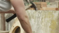 A young woman uses her muscles to hammer nails in 4K. video