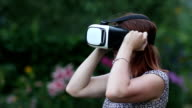 Young woman uses VR helmet with head mount display video