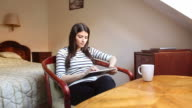 Young woman using a digital tablet in the bedroom. video