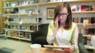 Young woman using a digital tablet in the bookstore. video