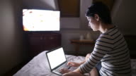 Young woman using a laptop while watching TV. video