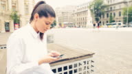 Young woman using a smart phone in the city. video