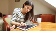 Young woman using a tablet and a smart phone in her living room. video
