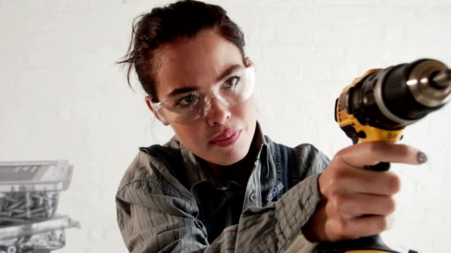 Young woman using an electric drill for DIY  PR video