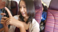 Young woman using cellphone on airplane video