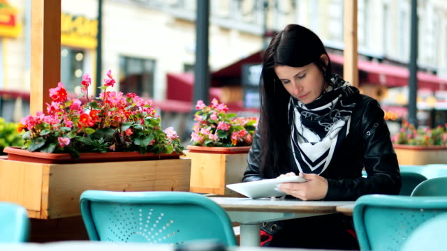 Young woman using digital tablet at street cafe video