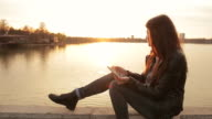 Young woman using digital tablet by the lake. video