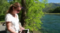 Young woman using digital tablet in nature video