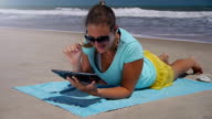 Young woman using digital tablet on the beach video